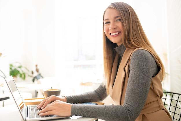 Jonge elegante zakenvrouw op zoek naar jou met brede glimlach tijdens het typen op laptop toetsenbord in café
