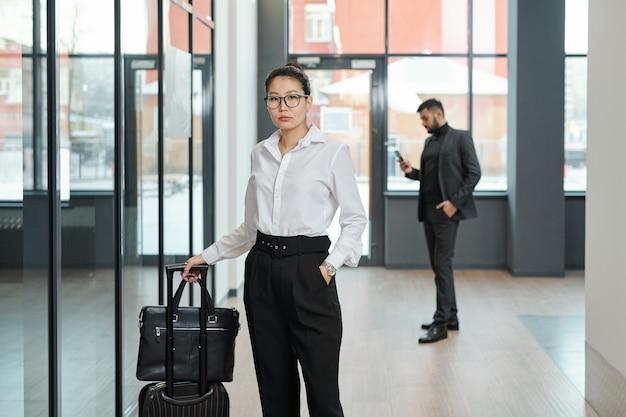 Jonge elegante zakenvrouw van aziatische afkomst koffer trekken in afwachting van vertrekaankondiging