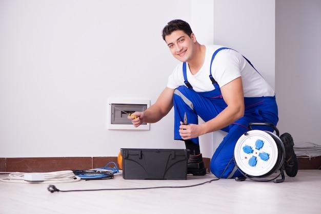 Jonge elektricien die aan contactdoos thuis werkt