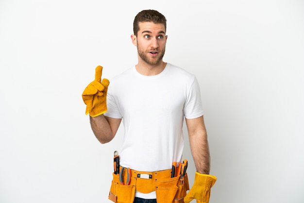 Jonge elektricien man isoleerde witte muur denkend aan een idee met de vinger omhoog