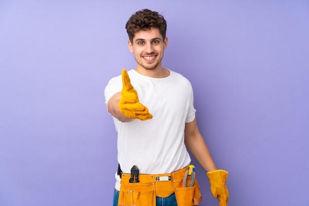 Jonge elektricien man over geïsoleerd op paarse handshaking na goede deal
