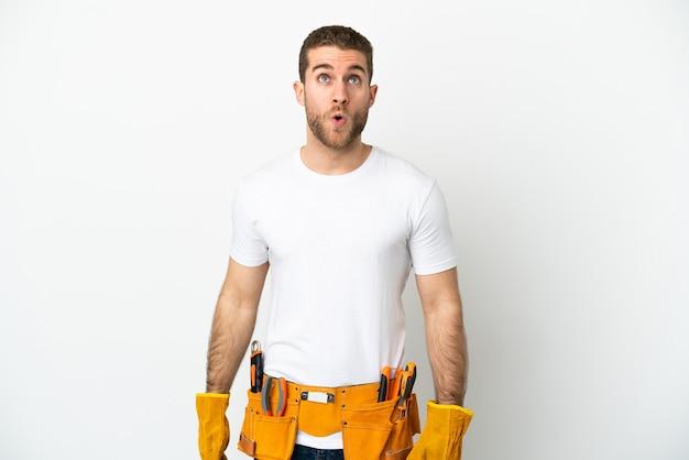 Jonge elektricien man over geïsoleerde witte muur opzoeken en met verbaasde uitdrukking