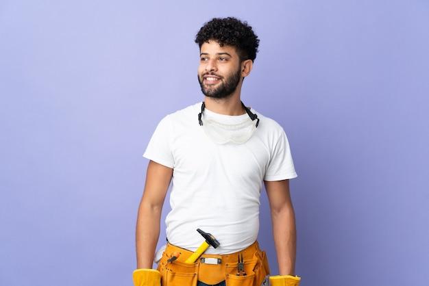 Jonge elektricien marokkaanse man geïsoleerd op paarse achtergrond die een idee denkt terwijl hij omhoog kijkt
