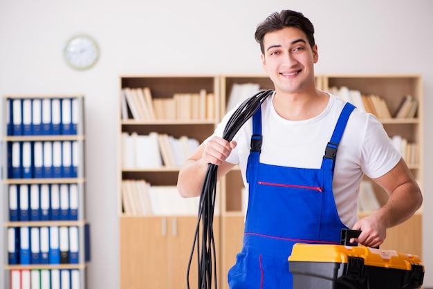 Jonge elektricien met kabel die in bureau werkt
