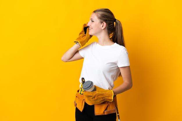Jonge elektricienvrouw die op de gele koffie van de muurholding en een mobiel wordt geïsoleerd