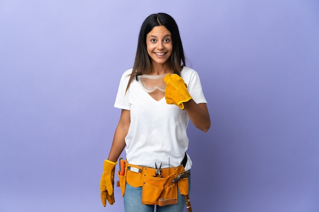 Jonge elektricienvrouw die op purpere muur met verrassingsgelaatsuitdrukking wordt geïsoleerd