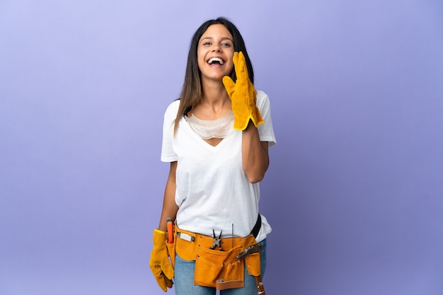 Jonge elektricienvrouw die op purpere muur wordt geïsoleerd die met wijd open mond schreeuwt
