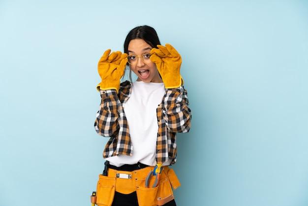 Jonge elektricienvrouw op blauwe muur met glazen en verrast