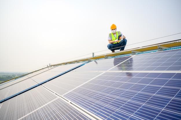 Jonge elektrotechnisch ingenieur werken in een fotovoltaïsche energiecentrale kwaliteit van zonnepanelen controleren en de elektriciteit in het gebouw regelen door een technicus van het fotovoltaïsche systeem
