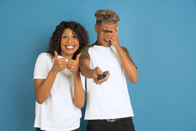 Jonge emotionele afro-amerikaanse man en vrouw die zich voordeed op blauwe achtergrond. mooi koppel. concept van menselijke emoties, gezichtsuitdrukkingen, relaties, advertentie. kijk samen tv, haar favoriete kanaal.