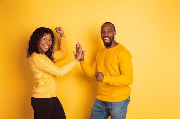 Jonge emotionele afro-amerikaanse man en vrouw in lichte vrijetijdskleding die zich voordeed op gele achtergrond. mooi koppel. concept van menselijke emoties, gezichtsuitdrukkingen, relaties, advertentie. teamwerk.