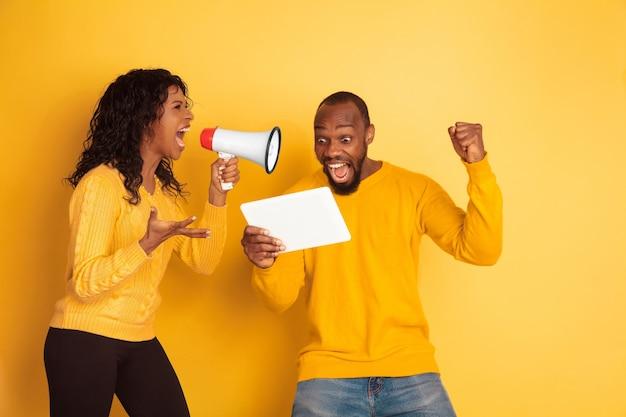 Jonge emotionele afro-amerikaanse man en vrouw op geel