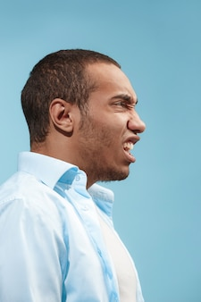 Jonge emotionele boze man op blauwe studio