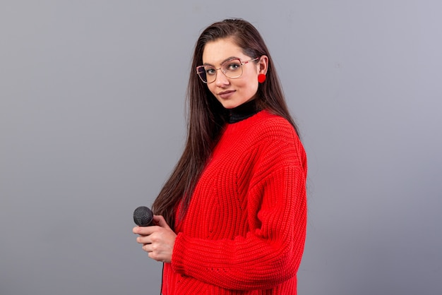 Jonge, emotionele brunette met een microfoon gekleed in een rode trui zingt karaoke of zegt een toespraak, geïsoleerd op grijs