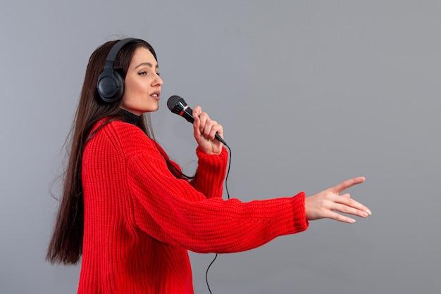 Jonge, emotionele brunette met koptelefoon en een microfoon gekleed in een rode trui zingt karaoke, geïsoleerd op grijs