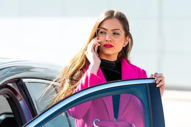 Jonge emotionele brunette vrouw stapt uit de auto en praat over de telefoon