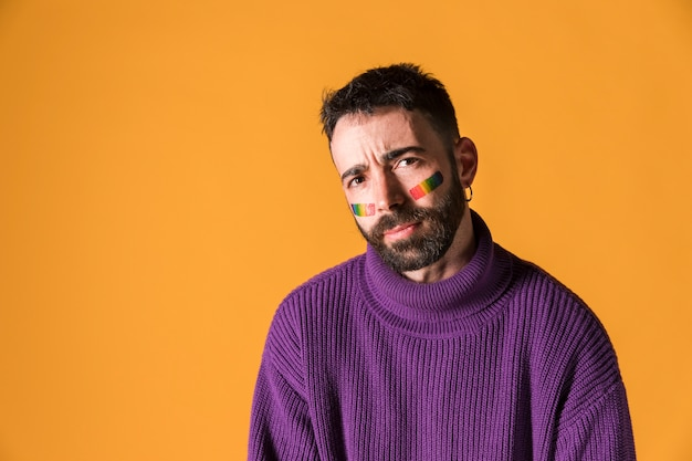 Jonge emotionele knappe man met lgbt-regenboogsymbool op gezicht