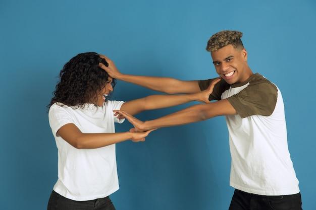 Jonge emotionele man en vrouw in witte vrijetijdskleding die zich voordeed op blauw.