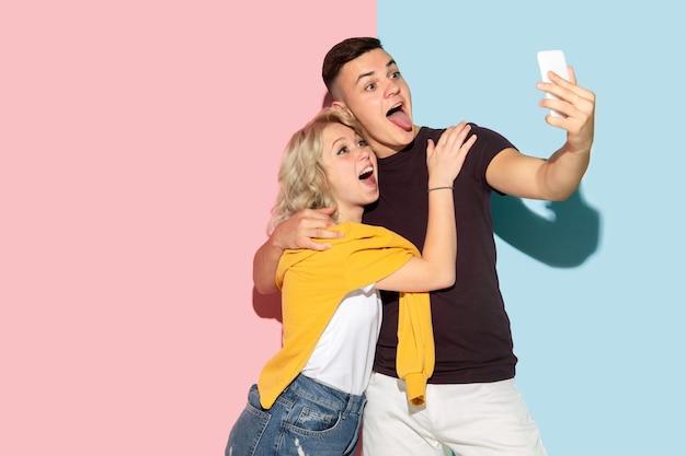 Jonge emotionele man en vrouw op roze en blauw