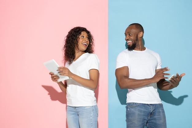 Jonge emotionele man en vrouw op roze en blauwe achtergrond