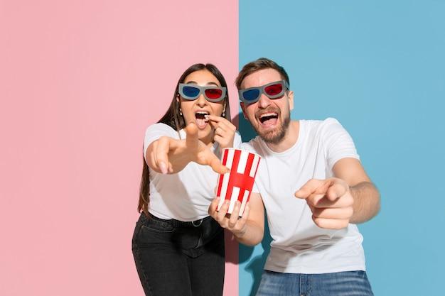 Jonge emotionele man en vrouw op roze en blauwe muur