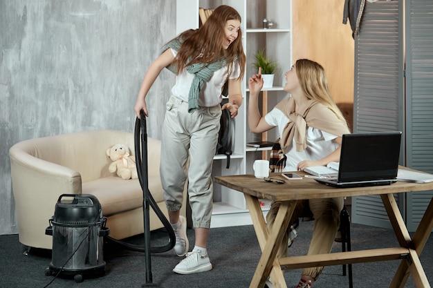 Jonge emotionele vrienden spelen met een stofzuiger terwijl ze huishoudelijk werk doen in huis