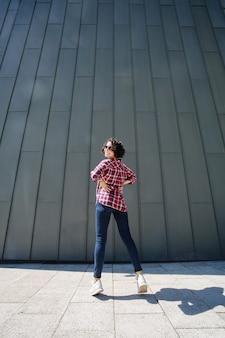 Jonge emotionele vrouw in een spijkerbroek en witte sneakers springen door de muur op de straat in de stad. portret van lachende meisje met krullend haar en zonnebril op grijze muur