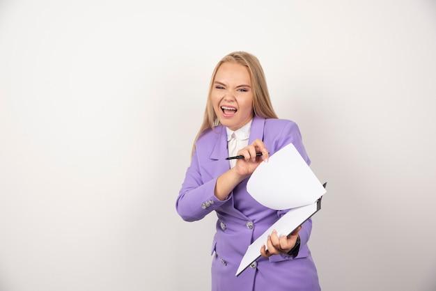 Jonge emotionele vrouw met potlood en tablet op wit.