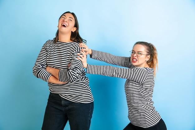 Jonge emotionele vrouwen die op de muur van de gradiënt de blauwe studio worden geïsoleerd