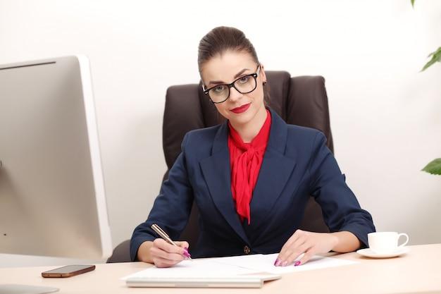 Jonge en aantrekkelijke bedrijfsvrouw die in bureau werkt