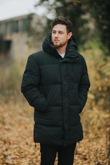 Jonge en aantrekkelijke man poseren in de natuur