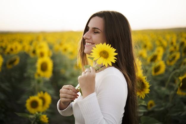 Jonge en aantrekkelijke vrouw die op een zonnige dag tussen de zonnebloemvelden in volle bloei staat