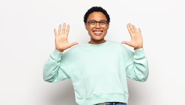 Jonge en afro-vrouw die vriendelijk glimlacht en kijkt, nummer tien of tiende met vooruit hand toont, aftellend