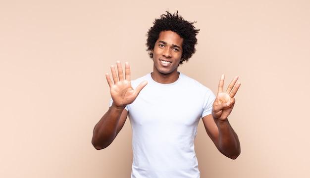 Jonge en afromens die vriendelijk glimlacht kijkt, nummer negen of negende met vooruit hand toont, aftellend