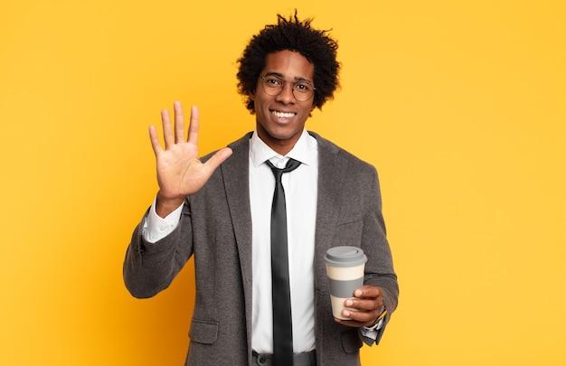 Jonge en afromens die vriendelijk glimlacht kijkt, nummer vijf of vijfde met vooruit hand toont, aftellend