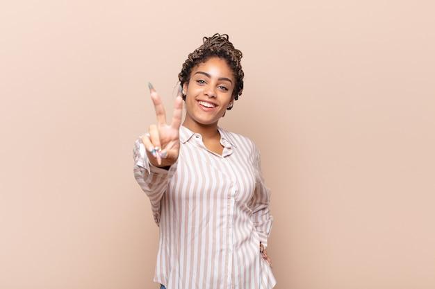 Jonge en afrovrouw die gelukkig, zorgeloos en positief geïsoleerd glimlacht kijkt