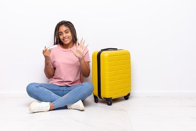 Jonge en afrovrouw die vriendelijk glimlacht kijkt, nummer vijf of vijfde met vooruit hand toont, aftellend. vakantie concept