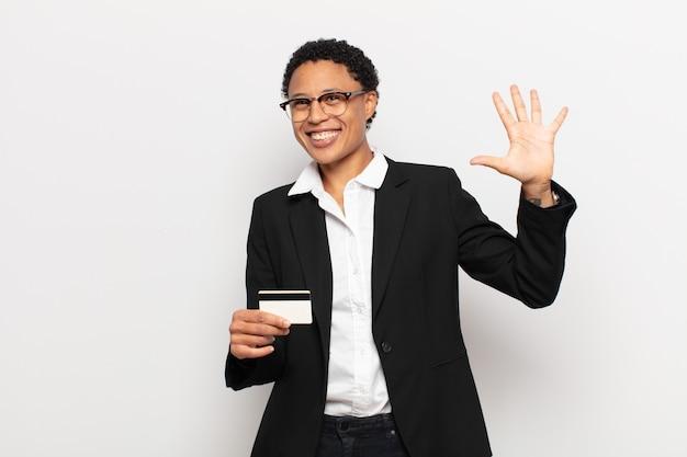 Jonge en afrovrouw die vriendelijk glimlacht kijkt, nummer vijf of vijfde met vooruit hand toont, aftellend