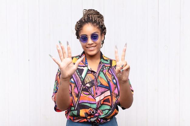 Jonge en afrovrouw die vriendelijk glimlacht kijkt, nummer zeven of zevende met vooruit hand toont, aftellend