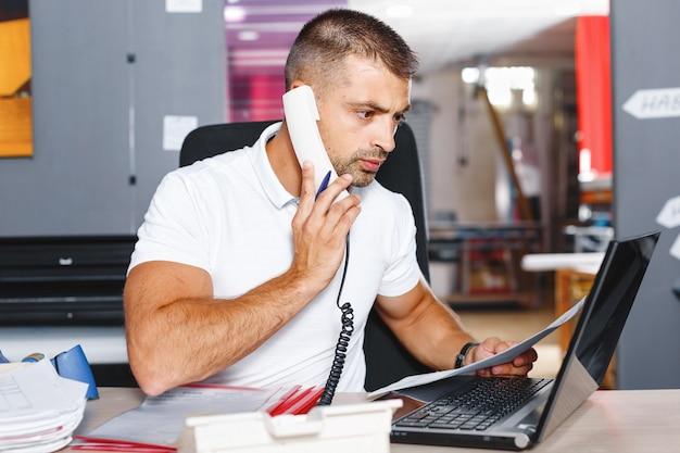 Jonge en ambitieuze beurshandelaar doet een deal via de telefoon in een druk kantoor vol computers.