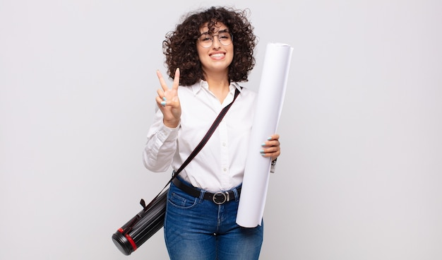 Jonge en architectenvrouw die vriendelijk glimlacht kijkt, nummer twee of seconde met vooruit hand toont, aftellend