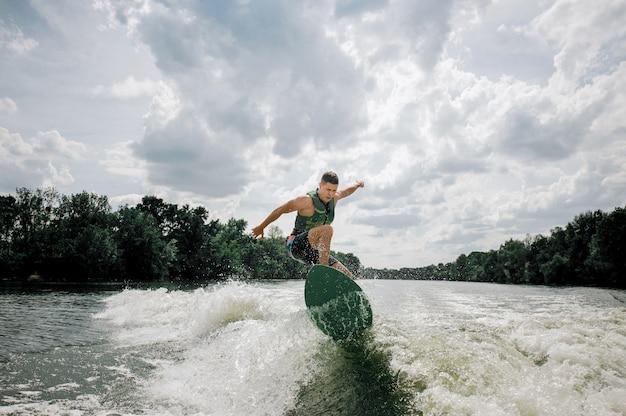 Jonge en atletische man wakesurfing op het bord