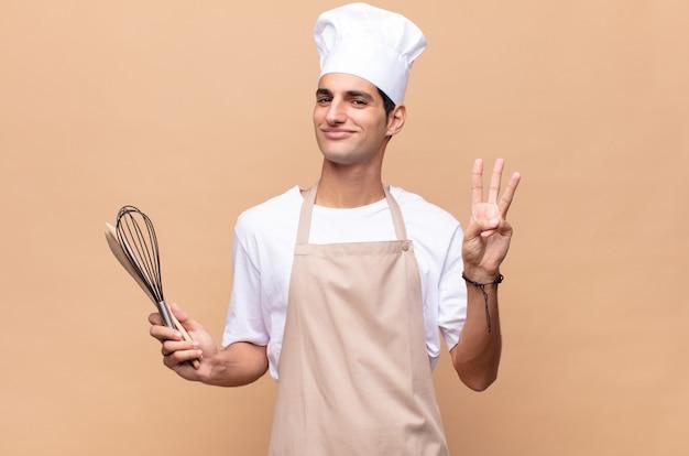 Jonge en bakkersmens die vriendelijk glimlacht kijkt, nummer drie of derde met vooruit hand toont, aftellend