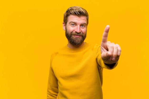 Jonge en blond mens die vriendelijk glimlacht kijkt, nummer één of eerst met vooruit hand toont, die tegen oranje muur aftelt