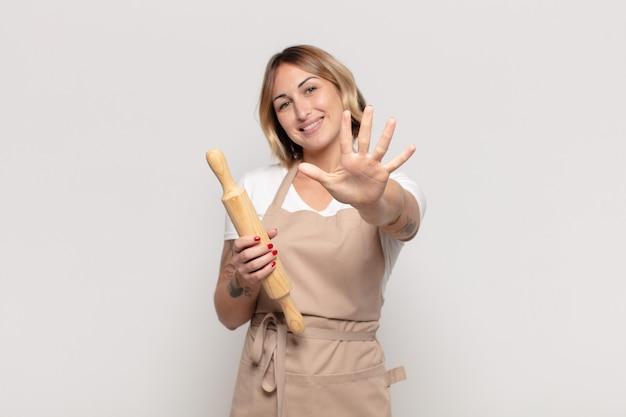 Jonge en blonde vrouw die vriendelijk glimlacht kijkt, nummer vijf of vijfde met vooruit hand toont, aftellend