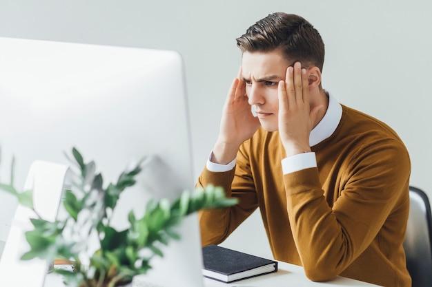 Jonge en charmante zakenman denkt aan zaken terwijl hij in zijn moderne kantoor zit