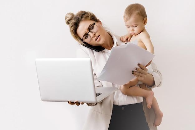 Jonge en drukke zakenvrouw werkt en houdt haar kleine baby vast. concepten van carrièreladder of zwangerschapsverlof.