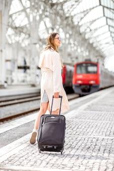 Jonge en elegante vrouw die terugloopt met bagage in de buurt van de trein op het moderne treinstation