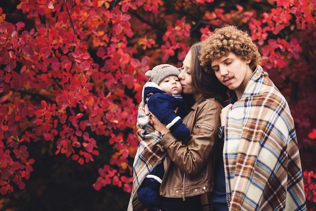 Jonge en gelukkige familie, bedekt met een deken, staat in de buurt van prachtige rode herfstbomen