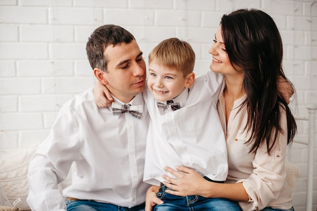 Jonge en gelukkige familie in een witte kamer, moeder, vader en zoontje